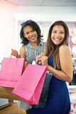 Two happy young ladies out shopping royalty free stock photography