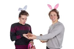 Two happy young men in a rabbit-like ears holding up basket with eggs. Happy Easter. Isolated on white background stock photography