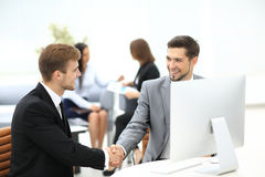 Two happy young men shaking hands while sitting at the office Royalty Free Stock Photo