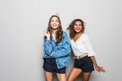 Two happy young mixed race woman in colorful clothes showing peace gesture, looking at camera, isolated over gray background royalty free stock image