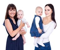 Two happy young mothers with little kids isolated on white stock photography