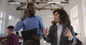Two happy young multiethnic man and woman, corporate business managers walk along modern loft office talking informally. stock video footage
