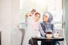 Two happy young muslim woman take self portrait with handphone at cafe Royalty Free Stock Image