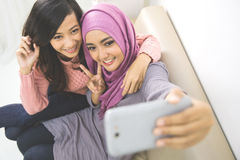 Two happy young muslim woman take self portrait Stock Image