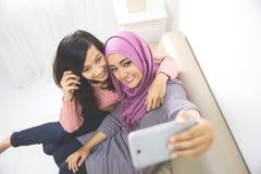 Two happy young muslim woman take self portrait Stock Photo