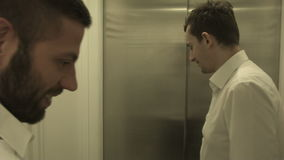 Two happy young people in an elevator. HD stock video footage