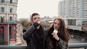 Two happy young people have fun. Handsome young man and beautiful girl laugh joyfully, holding takeaway coffee. City at the background stock video footage