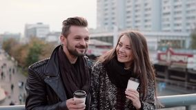 Two happy young people have fun. Handsome young man and beautiful girl laugh joyfully, holding takeaway coffee. Slow mo. Two happy young people have fun stock footage