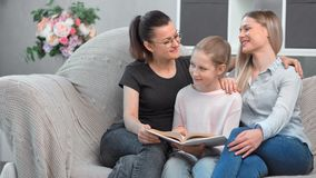 Two happy young smiling same sex mother reading book with their daughter at domestic interior stock footage