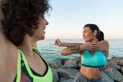 Two happy young sportswomen stretching hands Royalty Free Stock Image