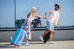 Two happy young tourists holding hands and running in front of an airport terminal. royalty free stock photography