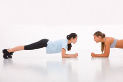 Two happy young woman doing push-ups in gym Stock Image