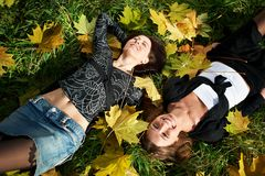 Two happy young woman on grass and yellow leaves Stock Photo