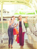 Two happy young woman are holding shopping bags in the city. Two happy young women are holding shopping bags in the city. Lifestyle, friendship and shopping Royalty Free Stock Photography