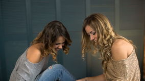 Two happy young woman look at the tablet and laughing stock video