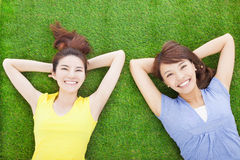 Two happy young woman resting on grass Stock Photography