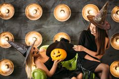 Two happy young women in black witch halloween costumes on party Royalty Free Stock Image