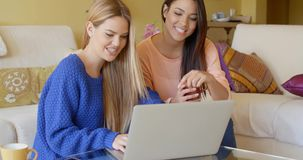 Two happy young women browsing the internet. Two happy gorgeous young women browsing the internet on a laptop computer as they spend a relaxing day at home in stock footage