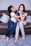 Two happy young women closely embracing while sitting on sofa in Royalty Free Stock Photos