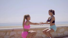 Two happy young women exercising together stock footage