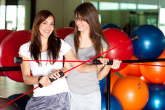 Two happy young women in the gym Stock Images