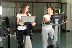 Two happy young women in the gym biking Royalty Free Stock Photography