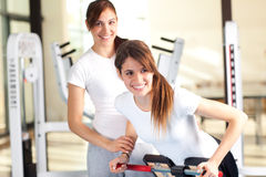 Two happy young women in the gym, selective focus Royalty Free Stock Image