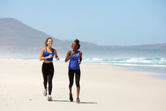 Two happy young women jogging on the beach Stock Photography