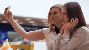 Two happy young women making selfie in the mall. Cute female friends take a selfie stock footage