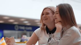 Two happy young women making selfie in the mall. Cute female friends take a selfie stock video footage