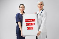 Doctor and nurse holding a poster with the inscription complex health care isolated on white background royalty free stock photos