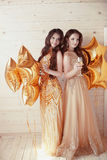 Two Happy Young Women On Party With Glasses Of Champagne. Cheerful Girls In Long Fashion Dress By Golden Stars Balloons Over Royalty Free Stock Images