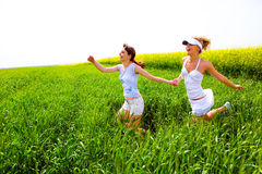Two happy young women are runing in a field.  Stock Photo