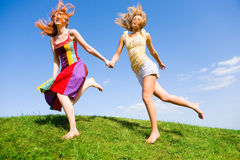 Two happy young women are runing in a field Stock Images