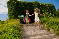 Two happy young women are runing in a park Royalty Free Stock Photo