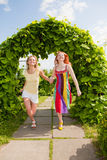 Two happy young women are runing in a park Royalty Free Stock Images