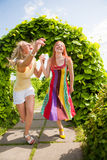 Two happy young women are runing in park stock images