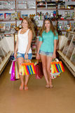 Two happy young women with shopping bags. Inside shop Royalty Free Stock Photo