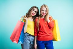 Two happy young women with shopping bags on blue background look with smile. Sale, shopping, tourism and happy people Stock Images