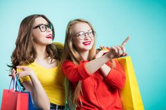 Two happy young women with shopping bags. Sale, shopping, emotions Royalty Free Stock Photos