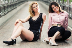 Two happy young women sitting on the sidewalk Royalty Free Stock Photos