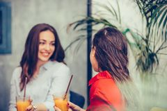 Two happy young women talking and drinking fresh fruit juice in a cafe royalty free stock photography