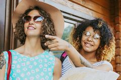 Two happy young women together. Head and shoulders portrait of two happy young women in sunglasses and sunhat, one pointing Royalty Free Stock Images
