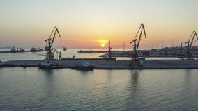 Two harbor cranes with the sun rising in between stock image