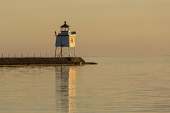 Two Harbors Breakwater Lighthouse. A lighthouse on a breakwater at sunset royalty free stock photography