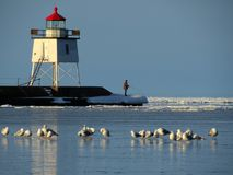 Two Harbors Lighthouse. A lone fisherman hopes spring is not too far away as the ice fails to give up its winter grip on the Two Harbors, Minnesota harbor on Stock Photo