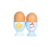 Two hard boiled eggs in cups. With childhood pictures, white background Royalty Free Stock Images