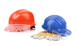 Two hard hats with working gloves Royalty Free Stock Photos