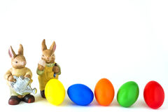 Two hares with coloured Easter eggs. Before white background Stock Image