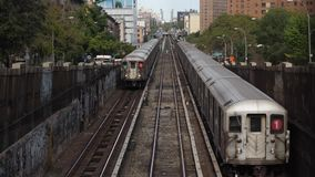 Two Harlem Bound Subway Trains Pass. 9409 Two Harlem bound subway trains pass each other in upper Manhattan on an elevated track on Broadway on a summer day stock footage